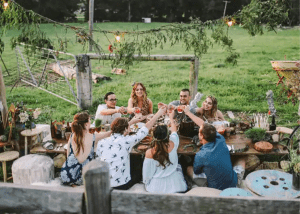 Friends sitting around an outdoor table sharing a meal at the Shed at Broger's End Kangaroo Valley